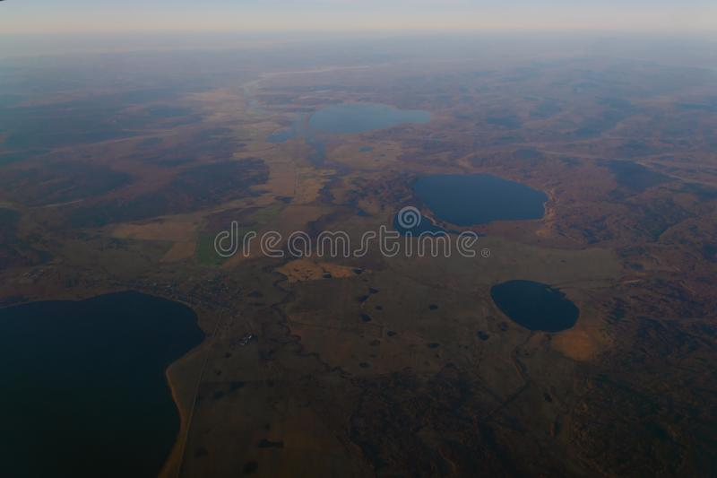 View from the window of the plane to the horizon of the lake and the river in the mountains with forests at sunset of the day royalty free stock photography
