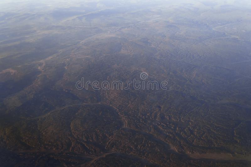 View from the window of the plane to the horizon of the lake and the river in the mountains with forests at sunset of the day royalty free stock images