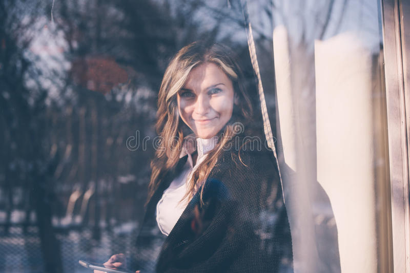 View through the window of a successful woman using a mobile phone. stock photo