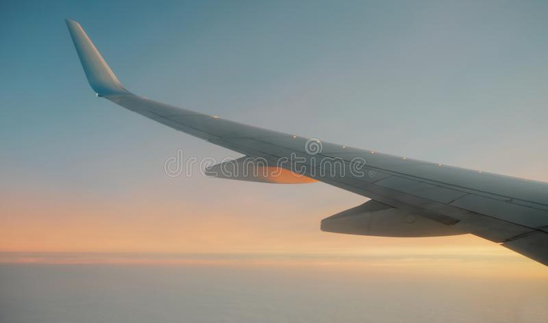 View from window at the sunset and airplane wing royalty free stock image