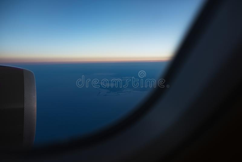 View from the window to airplane engine on runway of airport. Above the sky, on sunrise stock image
