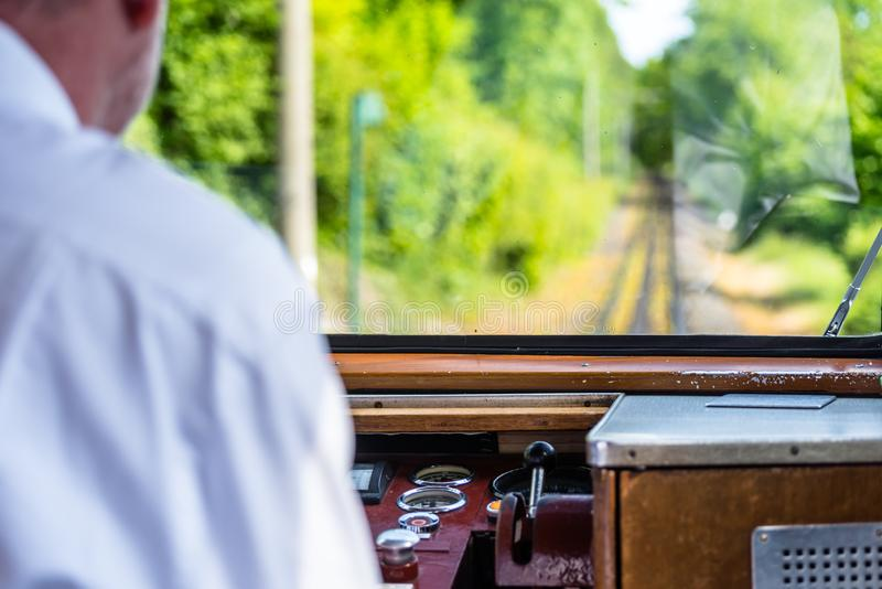 A view from the window of a traveling railroad train, a visible engine driver running a train, dashboard, tracks, trees and a blue stock photos