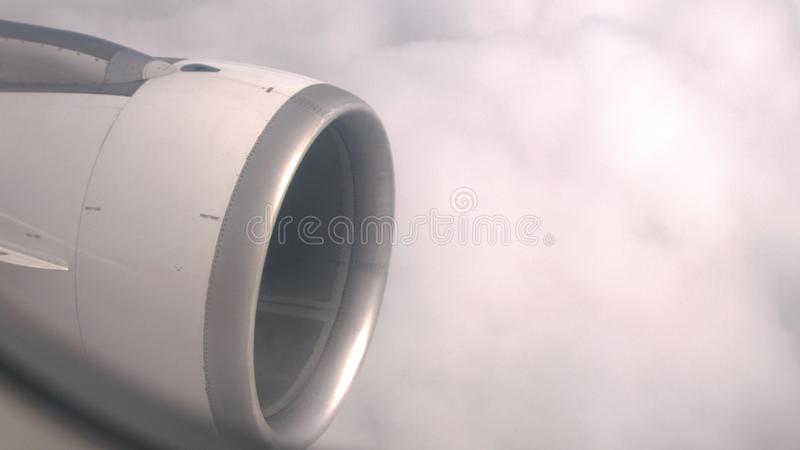 View through window at turbine plane against clouds. View through window at turbine plane and engine stock photos