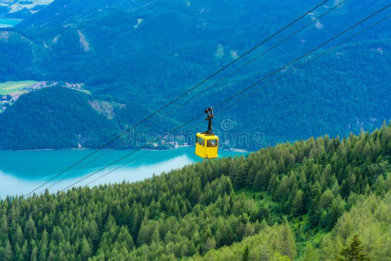 View of Wolfgangsee lake, mountains and yellow Seilbahn cable car gondola from Zwolferhorn mountain. View of Wolfgangsee lake, surrounding mountains and yellow stock photography