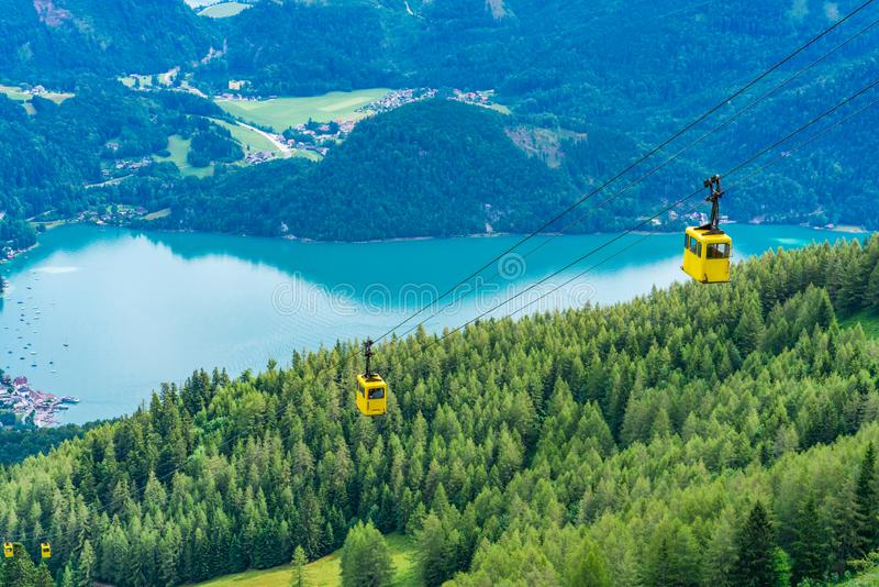View of Wolfgangsee lake, mountains and yellow Seilbahn cable car gondolas from Zwolferhorn mountain. In St. Gilgen in Salzkammergut region, Austria stock photos