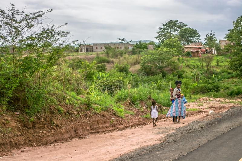 View of woman with children walks along roadside, typical African village as background stock photography
