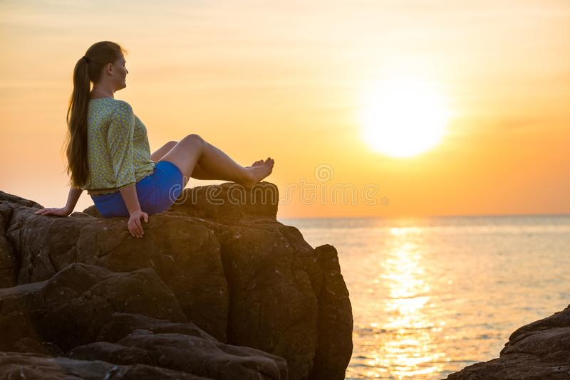 View of woman sitting on rock. Near sea and looking to beautiful sunset royalty free stock images