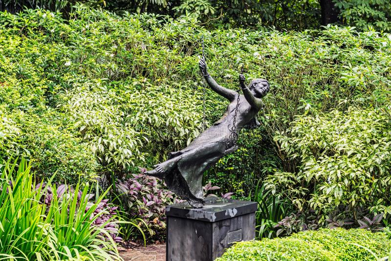 The women on a swing sculpture at Singapore Botanical Gardens. View at the women on a swing sculpture at Singapore Botanical Gardens royalty free stock images