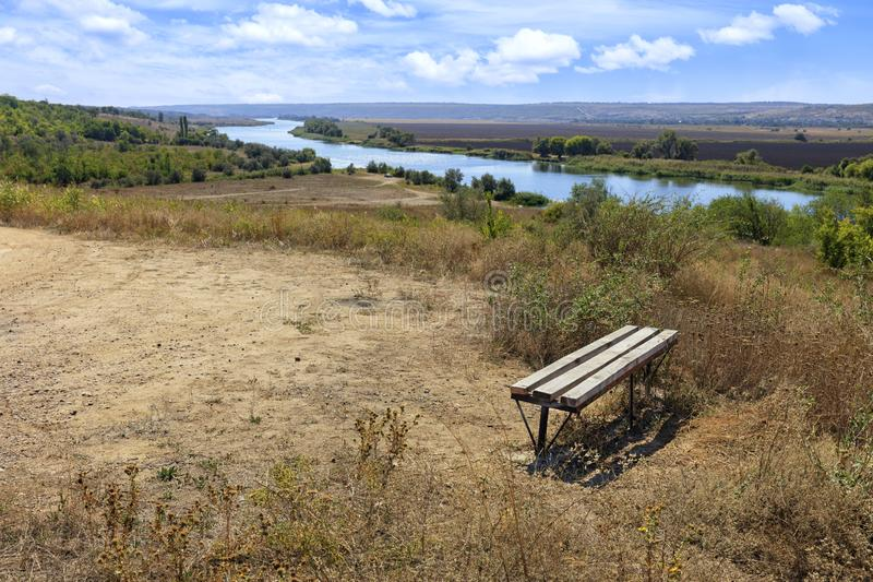 View of a wooden bench on a high river bank on a bright autumn day. Rural autumn landscape royalty free stock image