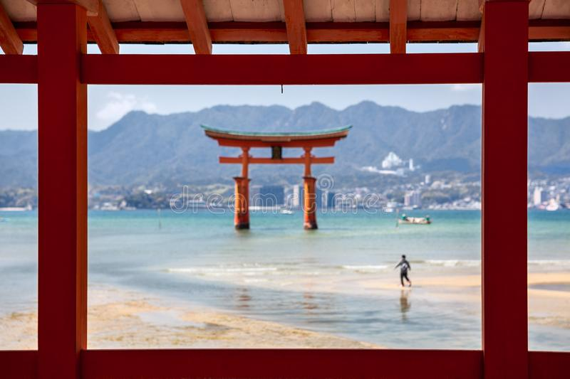 View through wooden constructions at the torii gate of Itsukushima Shrine in Miyajima island, Hiroshima, Japan. Low tide, blurred royalty free stock photo