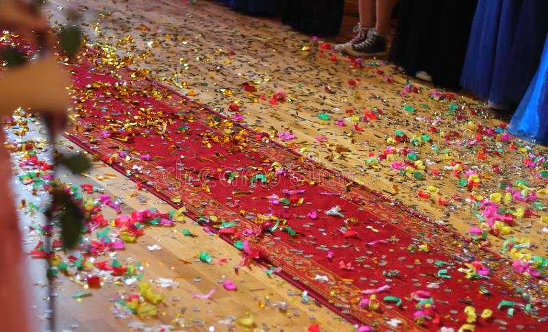 A view of a wooden floor with a strip of a red carpet full of coins, confetti and colored papers from celebration. stock photos