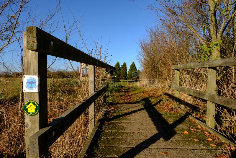 View of a wooden framed public footbridge seen at the side of a circular walk in a rural location. stock photo