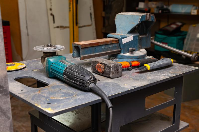 View of a workbench with a set of tools consisting of a large heavy vise, angle grinder, screwdriver, cutter, sledgehammer, and a. Spare cutting disc in a royalty free stock photography