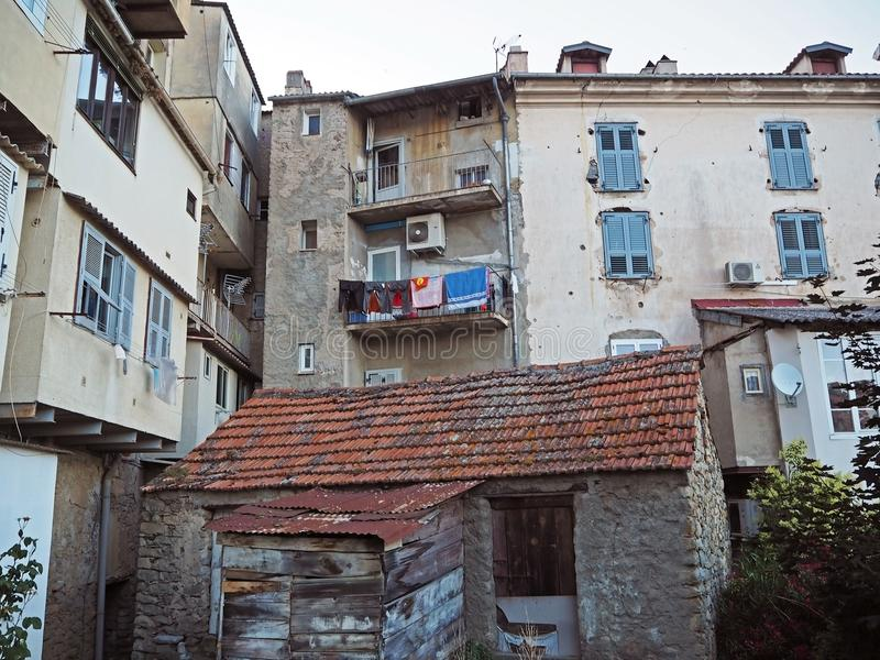 view on yard at old rental houses in corte city corsica with balcony and hanging clothes stock image