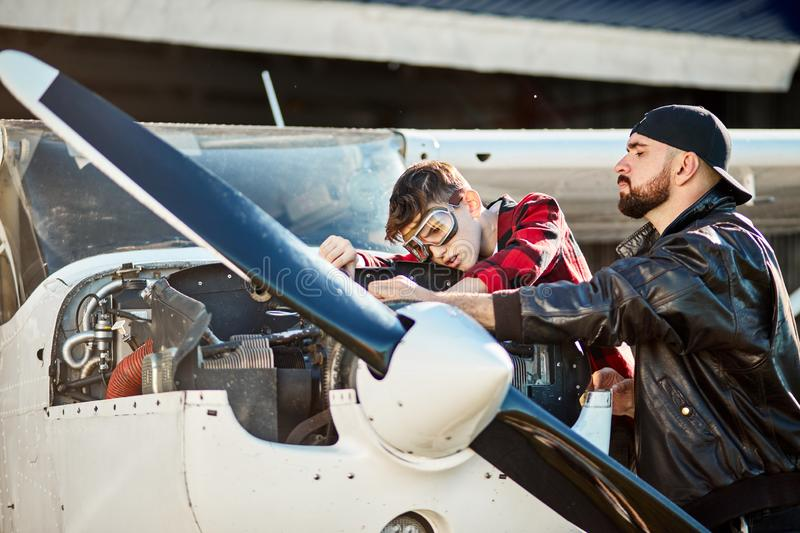 Aircraft male engineer with son making trouble-shooting of small propeller plane stock photography