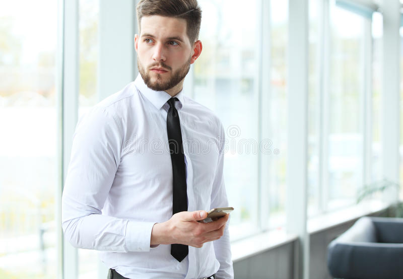 View of a Young attractive business man using smartphone. royalty free stock photography