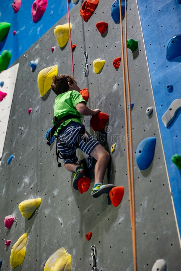 Young boy climbing up on practice wall in indoor rock gym royalty free stock images