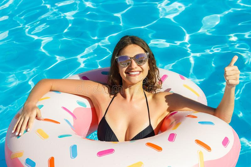 View of young brunette woman in black bikini swimming on the inflatable pink circle and thumb up royalty free stock image