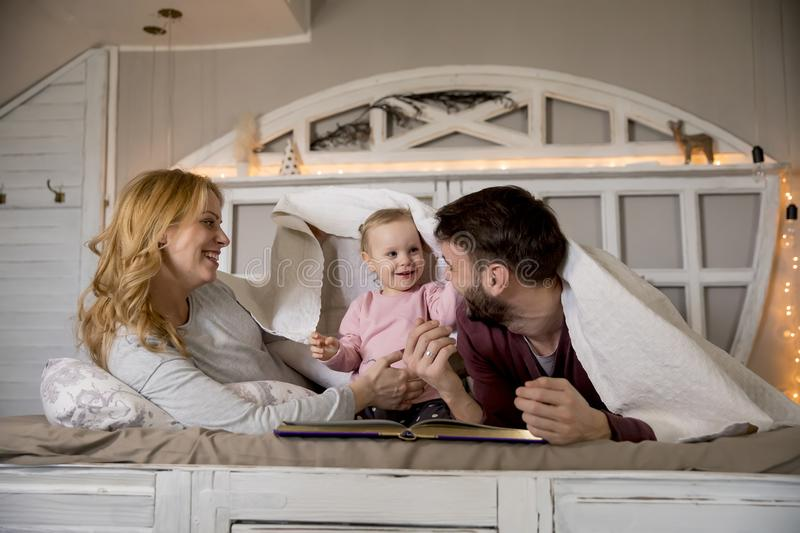 Young family having fun on bed in bedroom royalty free stock images
