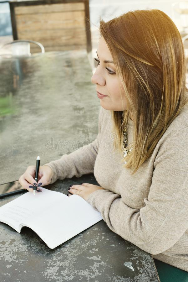 Hispanic Girl Millennial Writes Down Her Goals in a Journal in an Outdoor Cafe royalty free stock photos