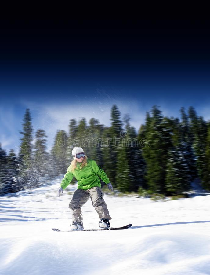 View of a young girl snowboarding in winter stock photography