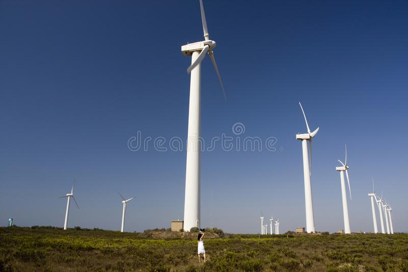 Girl and the windmill. View of a young girl watching a windmill stock photos