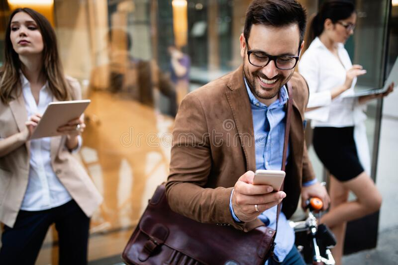 View at young business people talking and smiling outdoors royalty free stock image