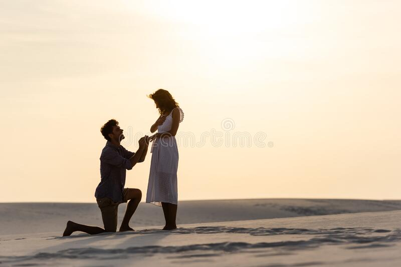 View Of Barefoot Passionate Young Couple Embracing On Beach Stock
