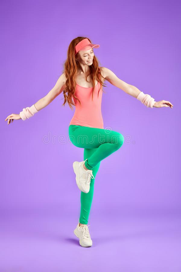 View of young red-haired aerobics girl dressed in 80s style. Red-headed girl with freckles in pink bodysuit, green leggins and pink sun cap doing aerobics stock images