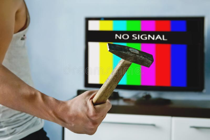 viewer is furious with the problems with broadcasting. Multi-colored stripes on the TV screen. The inscription on the TV NO SIGNAL stock photo