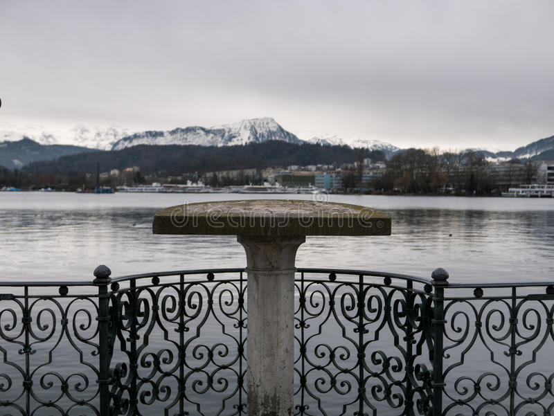 Viewing platform overlooking a lake and mountains. A viewing platform by the lake in Luzern stock photo