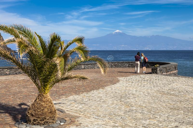 Viewing snow capped Mount Teide, Tenerife, from La Gomera. Two tourists viewing snow capped Mount Teide, Tenerife, from the shore of La Gomera stock photos