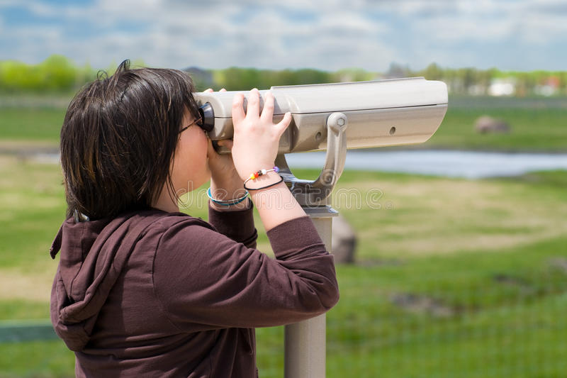 Viewpoint Coin Binoculars. A young girl looking through a set of viewpoint binoculars over prairie landscape stock image