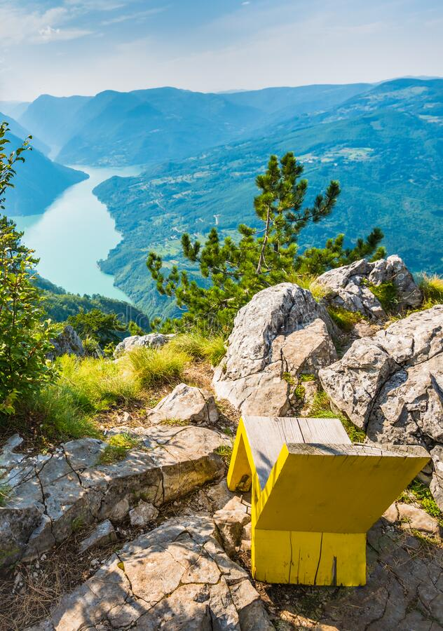 Viewpoint of green mountain valley and lake with cozy bench in Tara national park in Serbia. Great viewpoint of green mountain valley and lake with cozy bench to royalty free stock photography