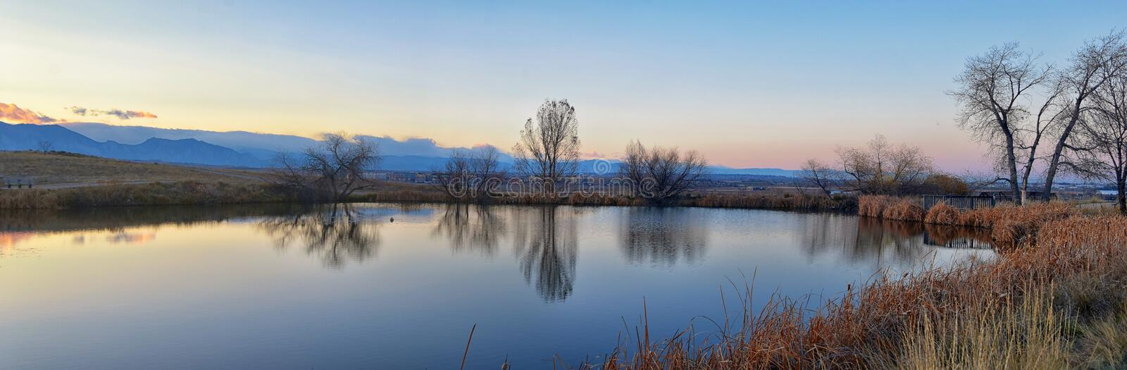 Views of Josh's Pond walking path, Reflecting Sunset in Broomfield Colorado surrounded by Cattails, plains and Rocky mountain la. Ndscape during sunset stock photography