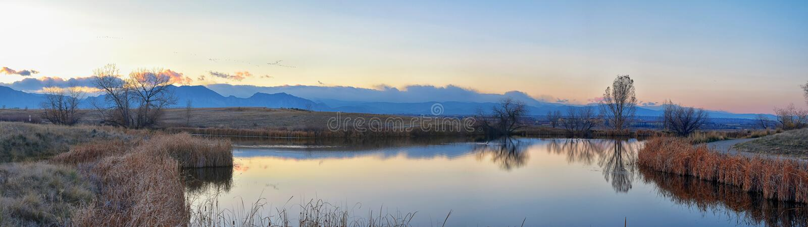 Views of Josh's Pond walking path, Reflecting Sunset in Broomfield Colorado surrounded by Cattails, plains and Rocky mountain la. Ndscape during sunset stock images