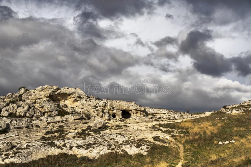 View of il Parco della Murgia e delle chiese rupestri close to Matera. Views of the Murgia and the stone churches Park with a meadow and few trails in foreground royalty free stock photos