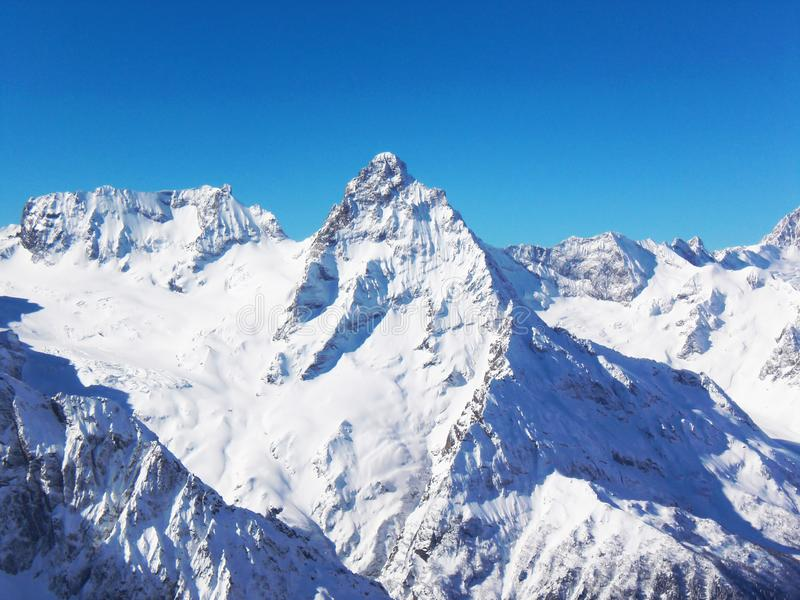 Views of snow capped mountains of Dombay. Winter Sunny day, mountain range, avalanche. Views of snow capped mountains of Dombay. Winter Sunny day, the Caucasus royalty free stock photos
