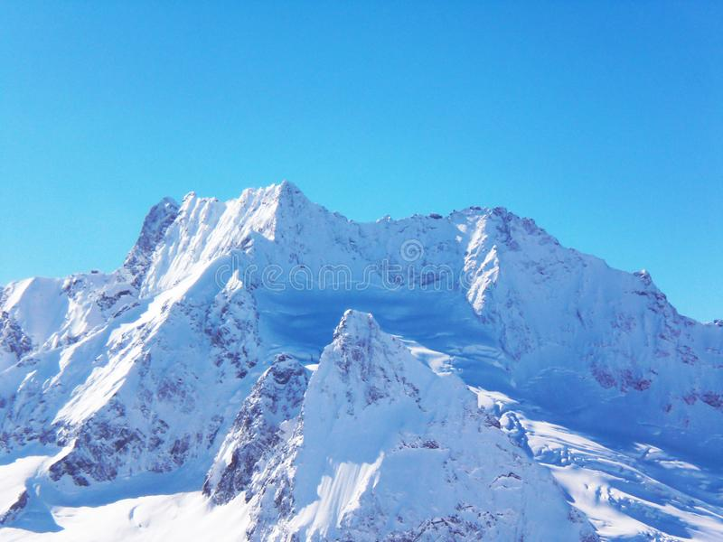 Views of snow capped mountains of Dombay. Winter Sunny day, mountain range, avalanche.  stock photography
