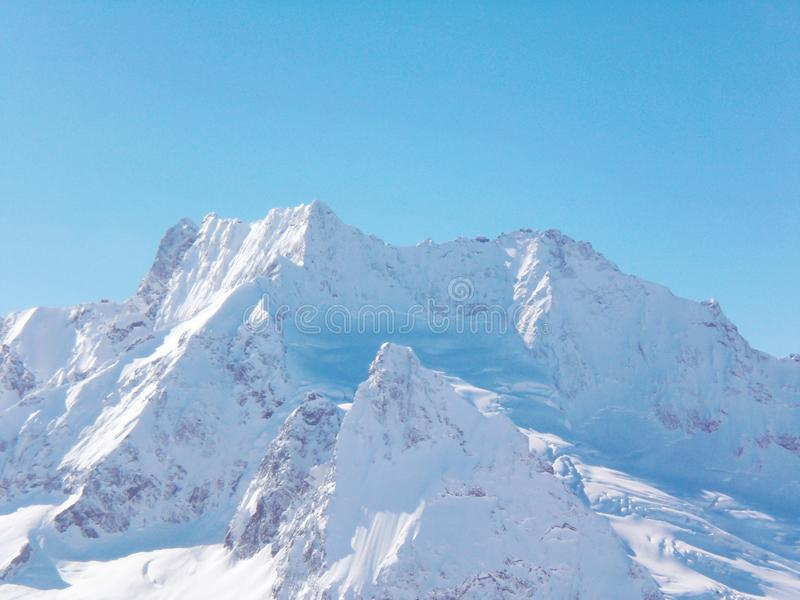Views of snow capped mountains of Dombay. Winter Sunny day, mountain range, avalanche.  stock photo