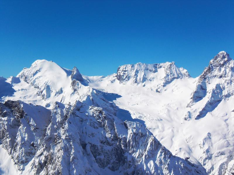 Views of snow capped mountains of Dombay. Winter Sunny day, mountain range, avalanche.  royalty free stock photo