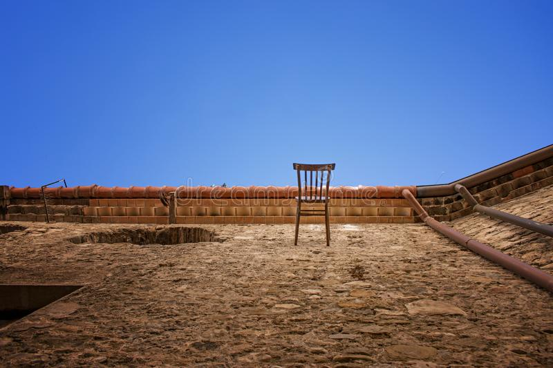 Views to the sky. An image where the point of view is deceptive. Really the chair is in a wall orientated towards the sky stock photo