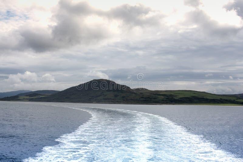 A vigília saiu por uma balsa que viaja ao longo da costa de Escócia em um dia de verões frio fotografia de stock