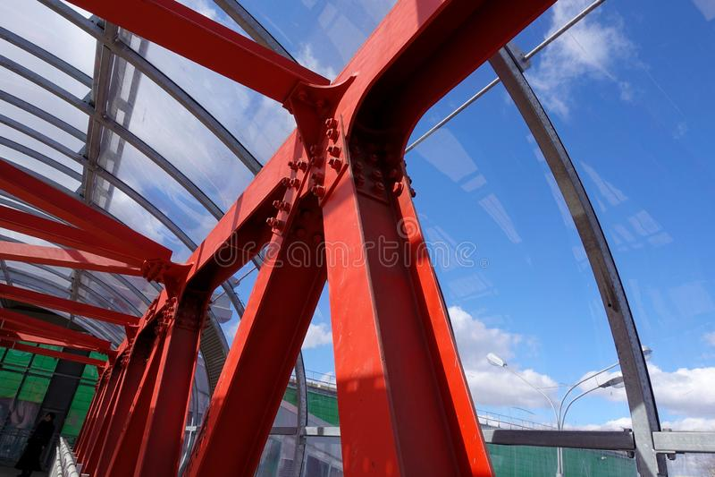 Vigas de aço no vermelho contra um céu azul Passagem aérea Fundo industrial foto de stock royalty free