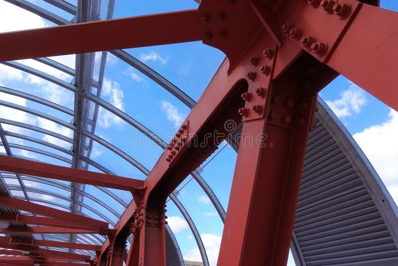 Vigas de aço no vermelho contra um céu azul Passagem aérea Fundo industrial foto de stock