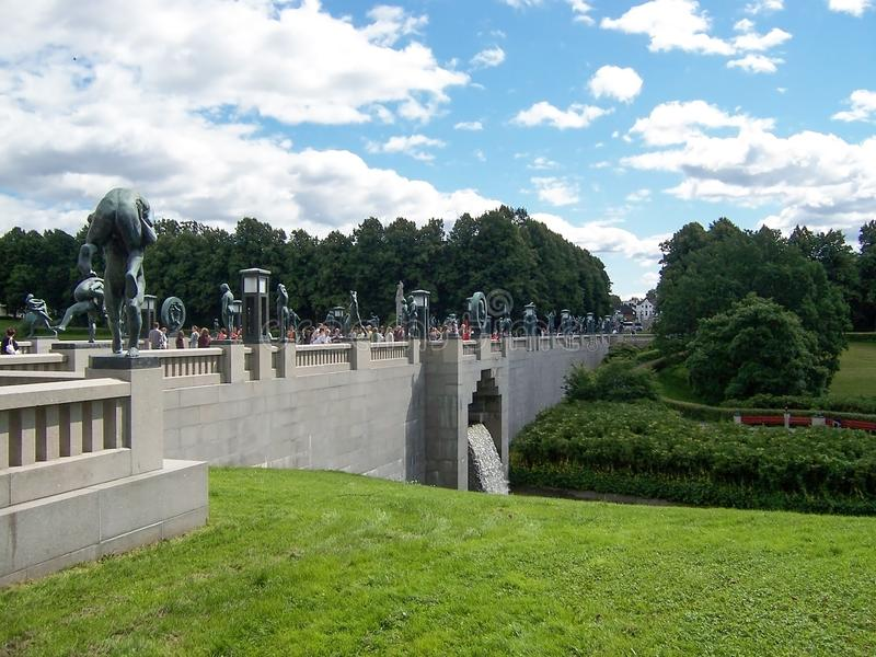 Vigelandsparken, Oslo, Noorwegen in Juli 2007: schilderachtig landschap met groene gazons en steenbrug in Vigeland-Park royalty-vrije stock afbeelding