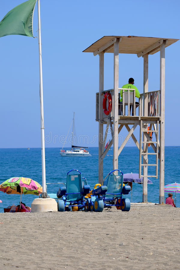 Vigilant lifeguard watches from his tower. royalty free stock photos
