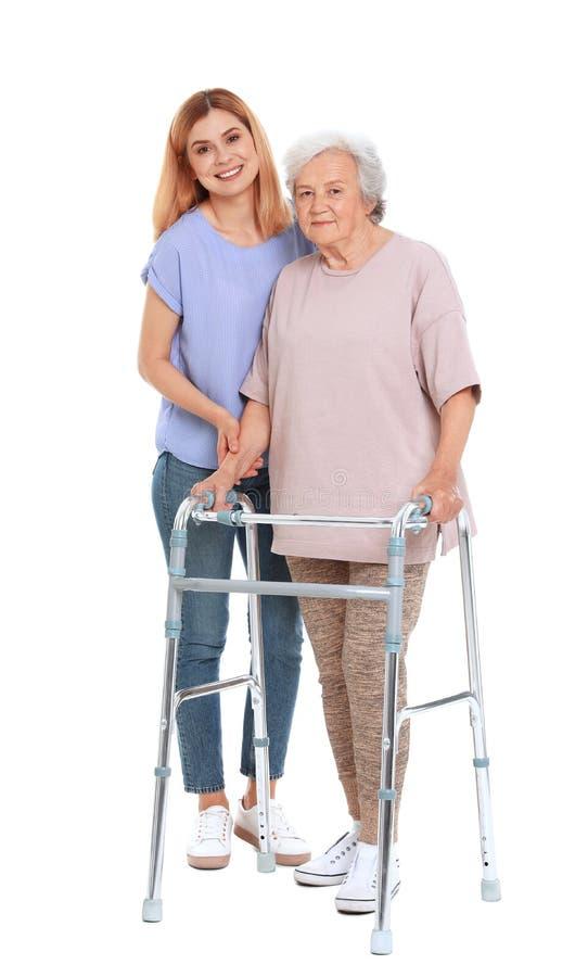 Vigilante que ayuda a la mujer mayor con el marco en el fondo blanco fotografía de archivo libre de regalías