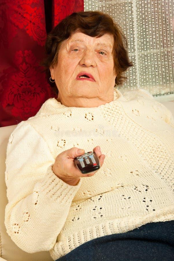 Vigilanza anziana TV della donna fotografia stock