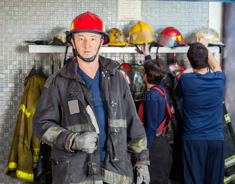 Vigile del fuoco sicuro che sta alla caserma dei pompieri fotografie stock libere da diritti